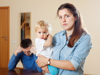 Sad woman with baby against husband after quarrel