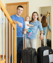 middle-aged couple with baby with luggage