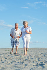 Old couple running on a beach