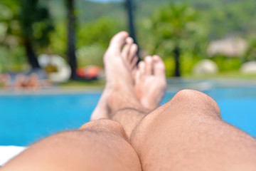 Men's legs close-up against  in the pool