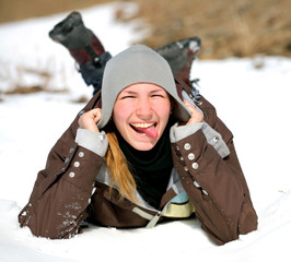 Close-up portrait of smiling young woman lying on a snow indicat