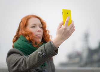 Young redhead girl taking a selfie outdoors.