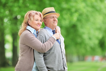 Carefree elderly couple hugging in park