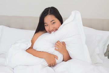 Smiling woman hugging her pillow