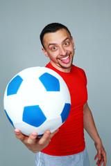 Funny sportive man holding soccer ball on gray background