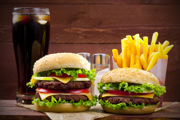 Two hamburgers with fries and cola on wood