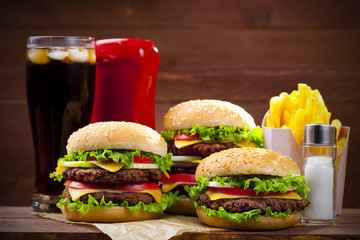 Three hamburgers with fries, cola and ketchup on wood
