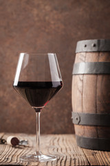 Glass with red wine and old barrel.