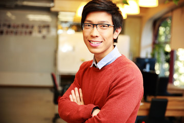 smiling asian man with arms folded standing in office