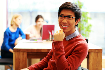 Young happy asian student sitting at the table