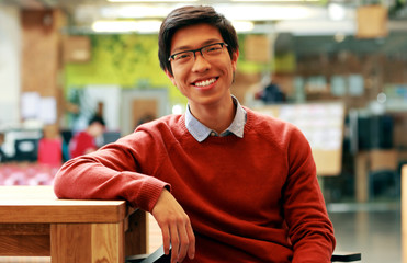 Young cheerful asian student sitting at the table