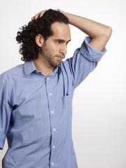 Junger Mexikaner in Hemd greift in Haare