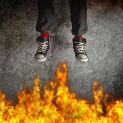 Young man in sneakers is jumping over fire