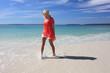 Happy woman splashing feet at the beach