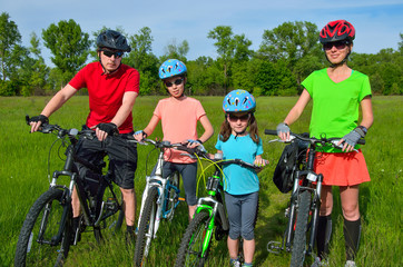 Happy family on bikes, cycling with kids