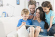 family playing together on a digital tablet - 64903253