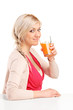 Girl sitting at table and drinking orange juice