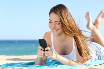 Pretty teenager girl using a smart  phone lying on the beach