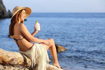 Woman on holidays  on the beach applying sunscreen protection