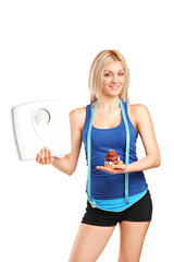 Woman holding a weight scale and a cake