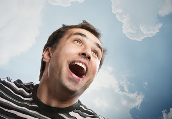 Portrait of a joyful man looking up against a sky background