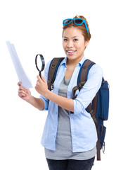 Happy traveler looking at guide with magnify glass