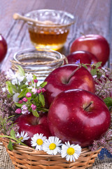 apples in a basket with honey and flowers on wooden table