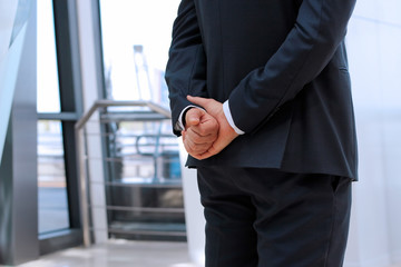 Businessman  standing  with both   hands behind