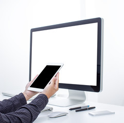 Hand holding tablet with computer background