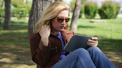 Woman using digital tablet in park