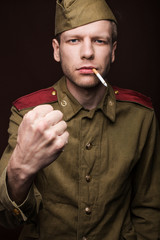 Russian soldier smoking cigarette and threaten with a fist
