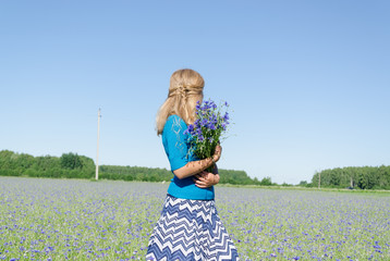 girl with bluet bouquet in wide meadow back view