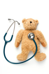 Bear doll and stethoscope on a white background