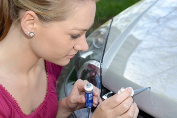 Frau repariert Kratzer im Auto-Lack