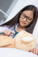Asian girl playing as a doctor with stethoscope and bear doll