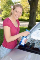 Frau reinigt Winschutzscheibe von Auto