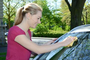 Frau putzt Auto-Scheibe mit Fensterleder