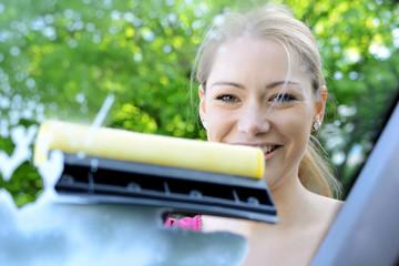 Frau reinigt Winschutzscheibe mit Abzieher