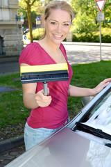Frau putzt Winschutzscheibe von Auto