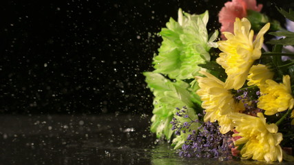 Bouquet of flowers falling onto wet black surface