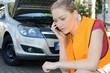 Leinwanddruck Bild - Frau in Warnweste telefoniert nach Panne