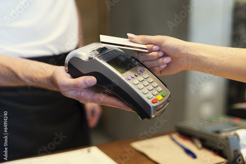 Close up of customer paying by credit card - 64914240