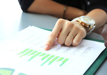 hand pointing at business document during discussion at meeting