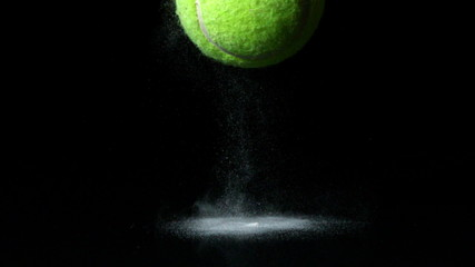 Tennis ball falling on black background
