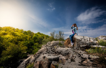 beautiful woman sitting on top of cliff and looking at sunset