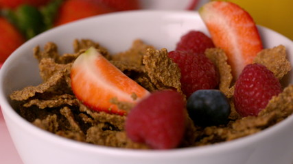 Berries pouring into cereal bowl at breakfast table