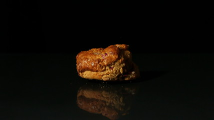 Scone falling on black background