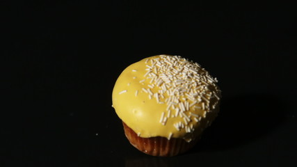 Yellow cupcake falling on black background