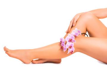 legs and hand with orchid flower. epilation