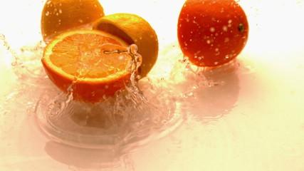 Lemon and orange halves falling and bouncing on white wet surfac